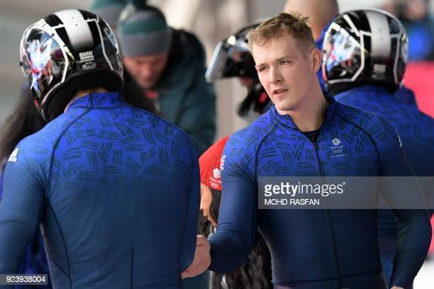 Britain's Brad Hall talks to a crew member after the 4man bobsleigh heat 4 final run during the Pyeongchang 2018 Winter Olympic Games at the Olympic...