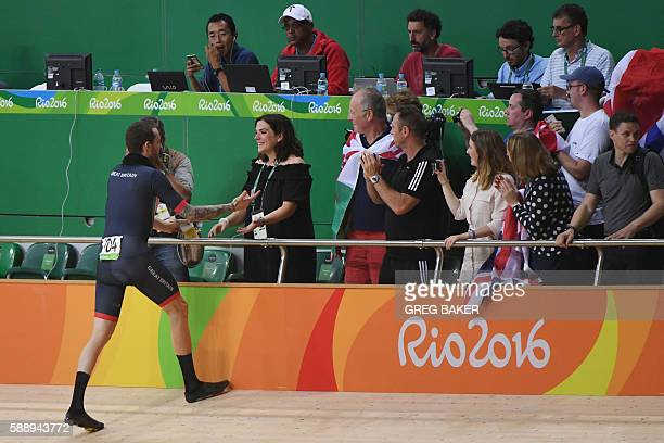 Britain's Bradley Wiggins reaches out to hug his wife Catherine Wiggins after winning gold in the men's Team Pursuit finals track cycling event at...