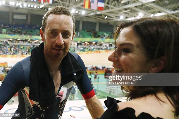 Britain's Bradley Wiggins speaks to his wife Catherine Wiggins after winning gold in the men's Team Pursuit finals track cycling event at the...