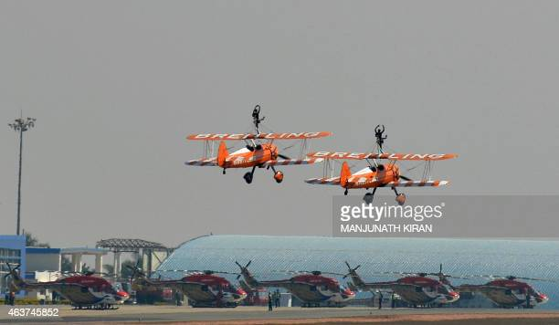 Britain's Breitling SkyWalkers Aerobatic Team perform aerial stunts atop Boeing Stearman Biplanes at Yelahanka Airforce Station in Bangalore on...