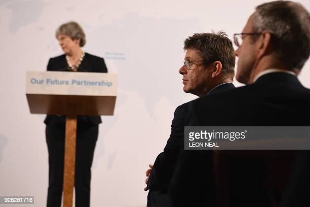 Britain's Business Secretary Greg Clark listens as British Prime Minister Theresa May gives a speech on Brexit at Mansion House in London on March 2...