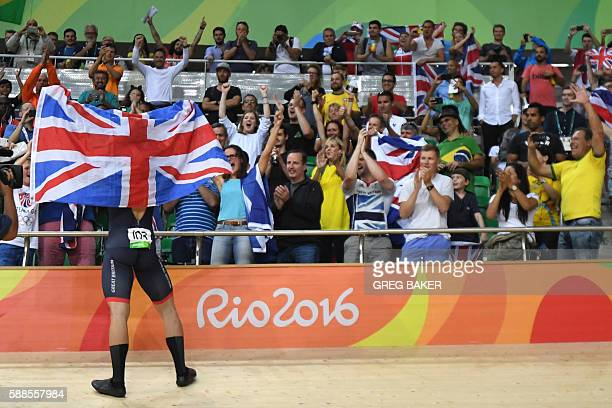 Britain's Callum Skinner holds up a flag as he celebrates after winning gold in the men's Team Sprint track cycling finals at the Velodrome during...