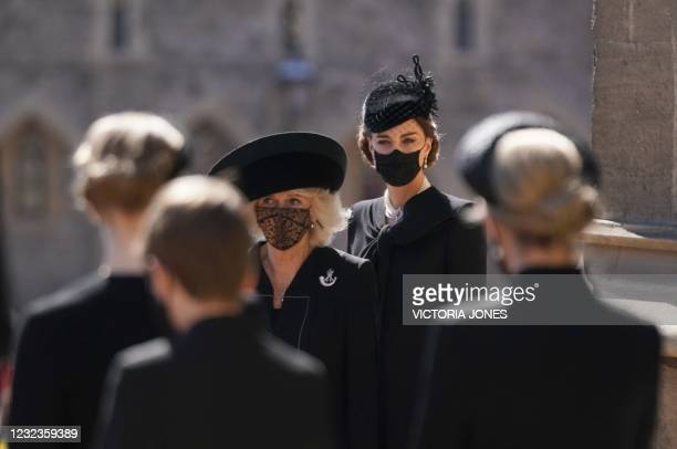 Britain's Camilla, Duchess of Cornwall and Britain's Catherine, Duchess of Cambridge stand outside St George's Chapel before the ceremonial funeral...