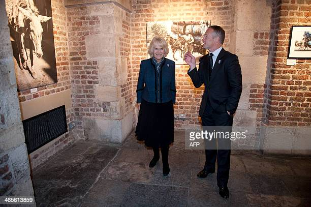 Britain's Camilla Duchess of Cornwall and retired jockey and photographer Richard Dunwoody look at photographs from the 'The Brooke through a lens'...