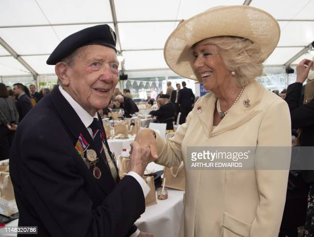 Britain's Camilla Duchess of Cornwall gets a kiss from DDay veteran 94 year old Ronald Wilson at a service of remembrance at Bayeux cemetery on June...