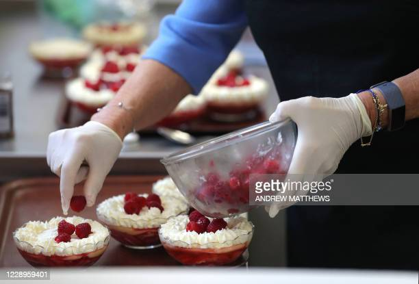 Britain's Camilla, Duchess of Cornwall, in her role as President, Royal Voluntary Service, places raspberries on a trifle dessert as she works in the...