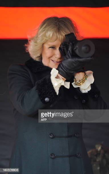 Britain's Camilla Duchess of Cornwall looks through a thermal scope as she is introduced to various pieces of military kit by British soldiers from R...