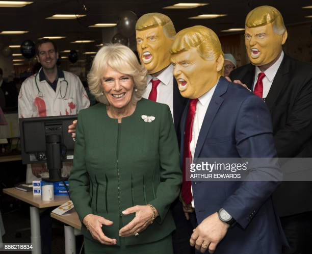 Britain's Camilla, Duchess of Cornwall poses with members of staff wearing Donald Trump masks during her visit to the offices of city traders ICAP on...