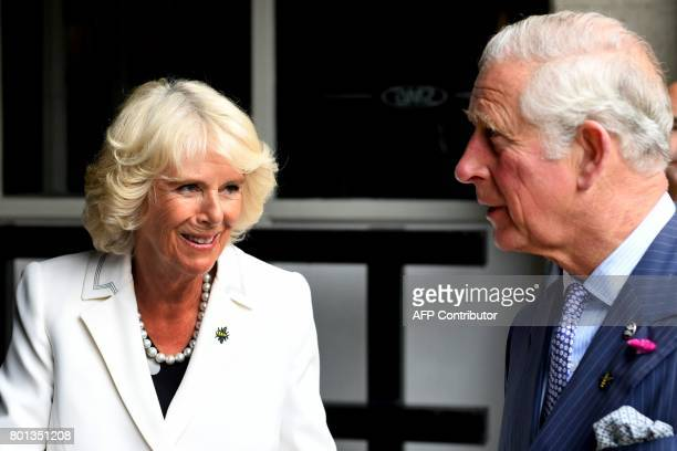 Britain's Camilla Duchess of Cornwall wears a broach in the shape of a Bee as she and her husband Britain's Prince Charles Prince of Wales leave the...