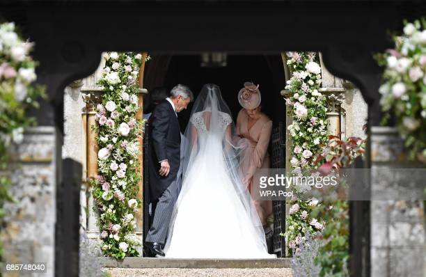 Britain's Catherine Duchess of Cambridge adjusts the dress of her sister Pippa Middleton as their father Michael Middleton stands by at the door to...