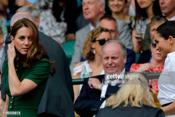 Britain's Catherine Duchess of Cambridge and Britain's Meghan Duchess of Sussex arrive to watch Romania's Simona Halep playing US player Serena...