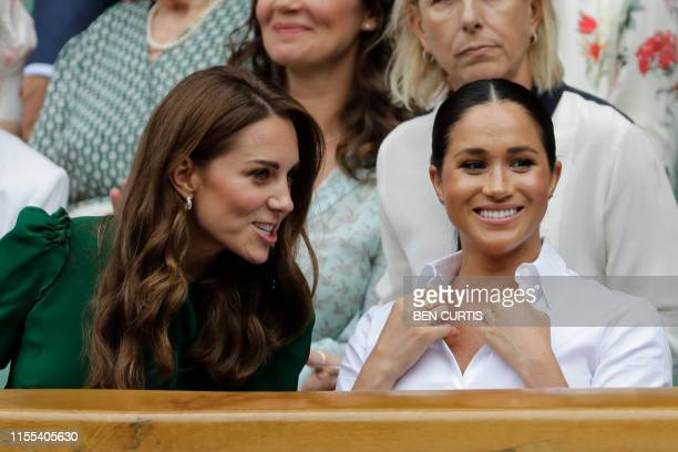 Britain's Catherine Duchess of Cambridge and Britain's Meghan Duchess of Sussex watch Romania's Simona Halep playing US player Serena Williams during...