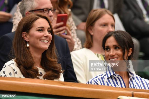 Britain's Catherine Duchess of Cambridge and Britain's Meghan Duchess of Sussex take their seat in the Royal box on Centre Court before watching...