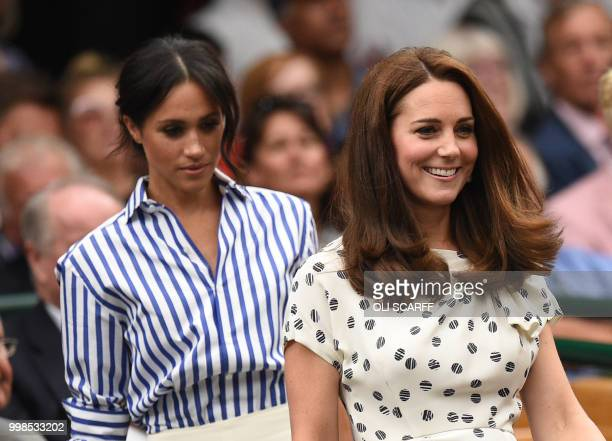 Britain's Catherine Duchess of Cambridge and Britain's Meghan Duchess of Sussex take their seats in the Royal box on Centre Court before watching...