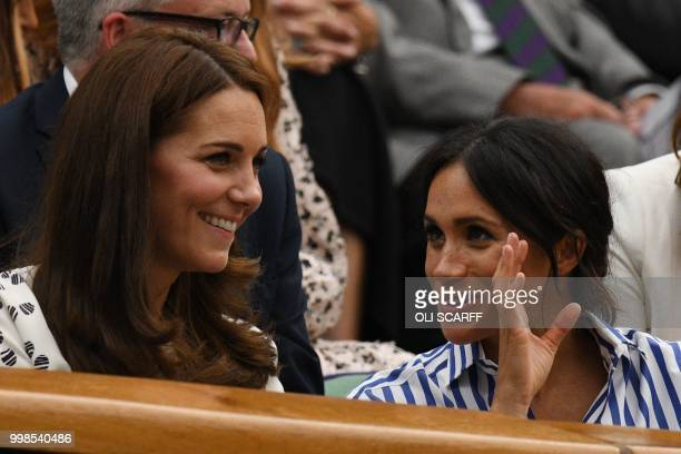 TOPSHOT Britain's Catherine Duchess of Cambridge and Britain's Meghan Duchess of Sussex react as they sit in the Royal box on Centre Court to watch...