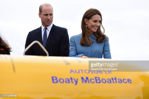 Britain's Catherine Duchess of Cambridge and Britain's Prince William Duke of Cambridge react as they stand near the unmanned submarine 'Boaty...