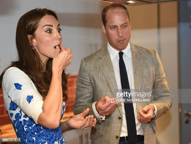 Britain's Catherine, Duchess of Cambridge and Britain's Prince William, Duke of Cambridge sample some cake during a visit Bute Mills in Luton, north...