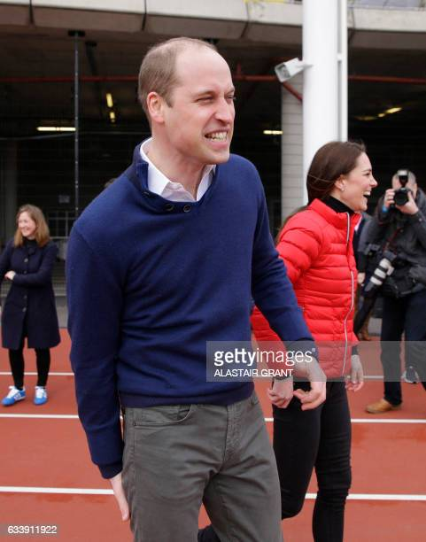 Britain's Catherine Duchess of Cambridge and Britain's Prince William Duke of Cambridge share a joke after running in a relay race during a training...