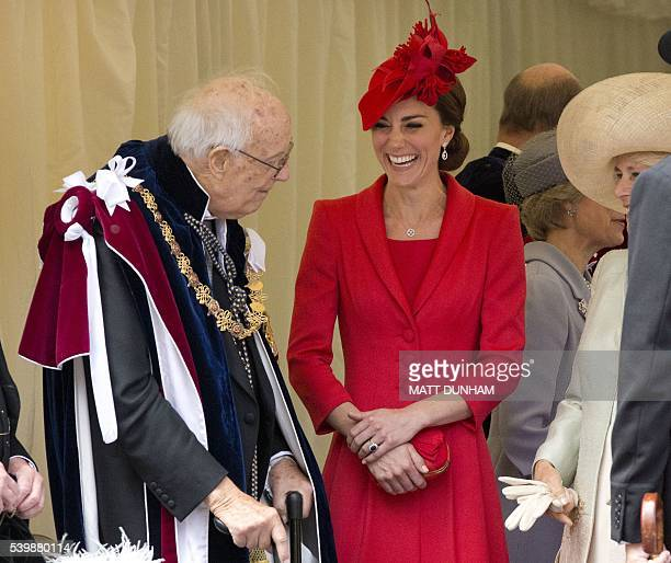 Britain's Catherine, Duchess of Cambridge and Camilla the Duchess of Cornwall , laugh as they talk with Lord Ashburton , as they wait for cars to...