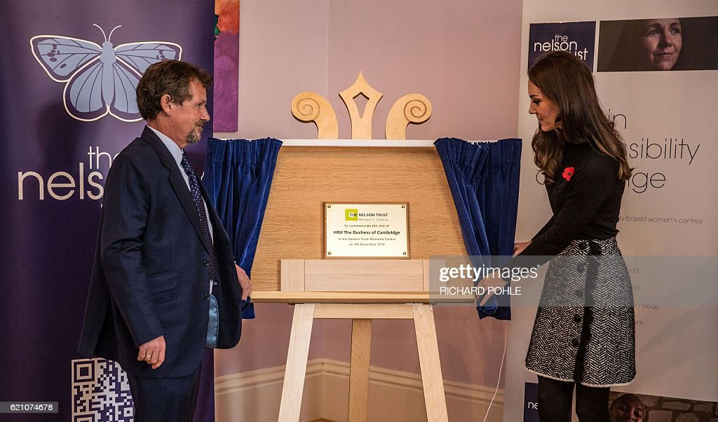 Britain's Catherine, Duchess of Cambridge (R) and Chief Executive of the Nelson trust John Trolan (L) unveil a plaque during a visit to the Nelson trust women centre in Gloucester, western England on November 4, 2016. The Women's Centre was set up in 2010 and is designed to support women who have vulnerabilities, particularly those who have experienced abuse and trauma. / AFP / POOL / RICHARD