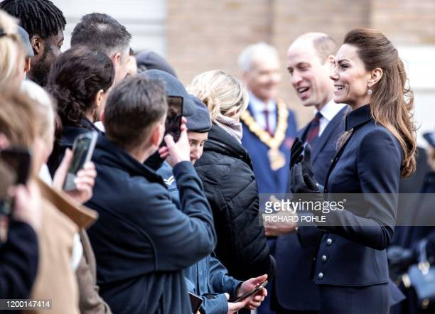 Britain's Catherine Duchess of Cambridge and her husband Britain's Prince William Duke of Cambridge talk to staff and patients during their visit to...