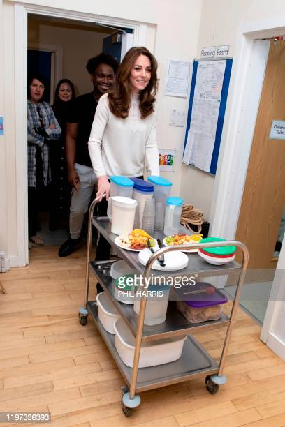 Britain's Catherine Duchess of Cambridge assists with breakfast during a visit to London Early Years Foundation at Stockwell Gardens Nursery and...