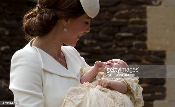 Britain's Catherine Duchess of Cambridge carries her daughter Princess Charlotte of Cambridge after taking her out of a pram as they arrive for...
