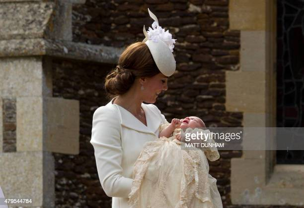 Britain's Catherine, Duchess of Cambridge, carries her daughter, Princess Charlotte of Cambridge after taking her out of a pram as they arrive for...