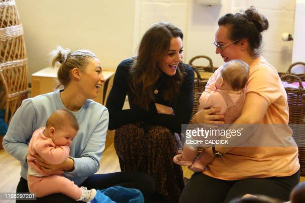 Britain's Catherine, Duchess of Cambridge chats with mothers and babied during her visit to the Ely & Caerau Children's Centre in Cardiff, south...