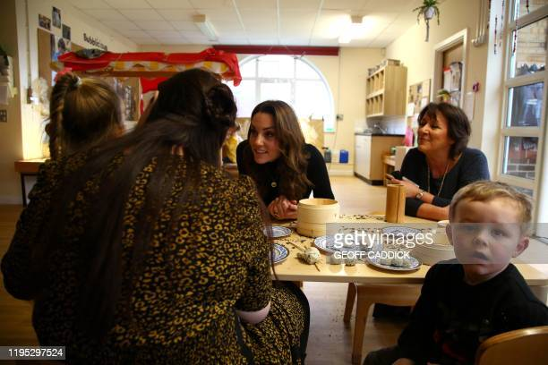 Britain's Catherine Duchess of Cambridge chats with mothers and their children during her visit to the Ely Caerau Children's Centre in Cardiff south...