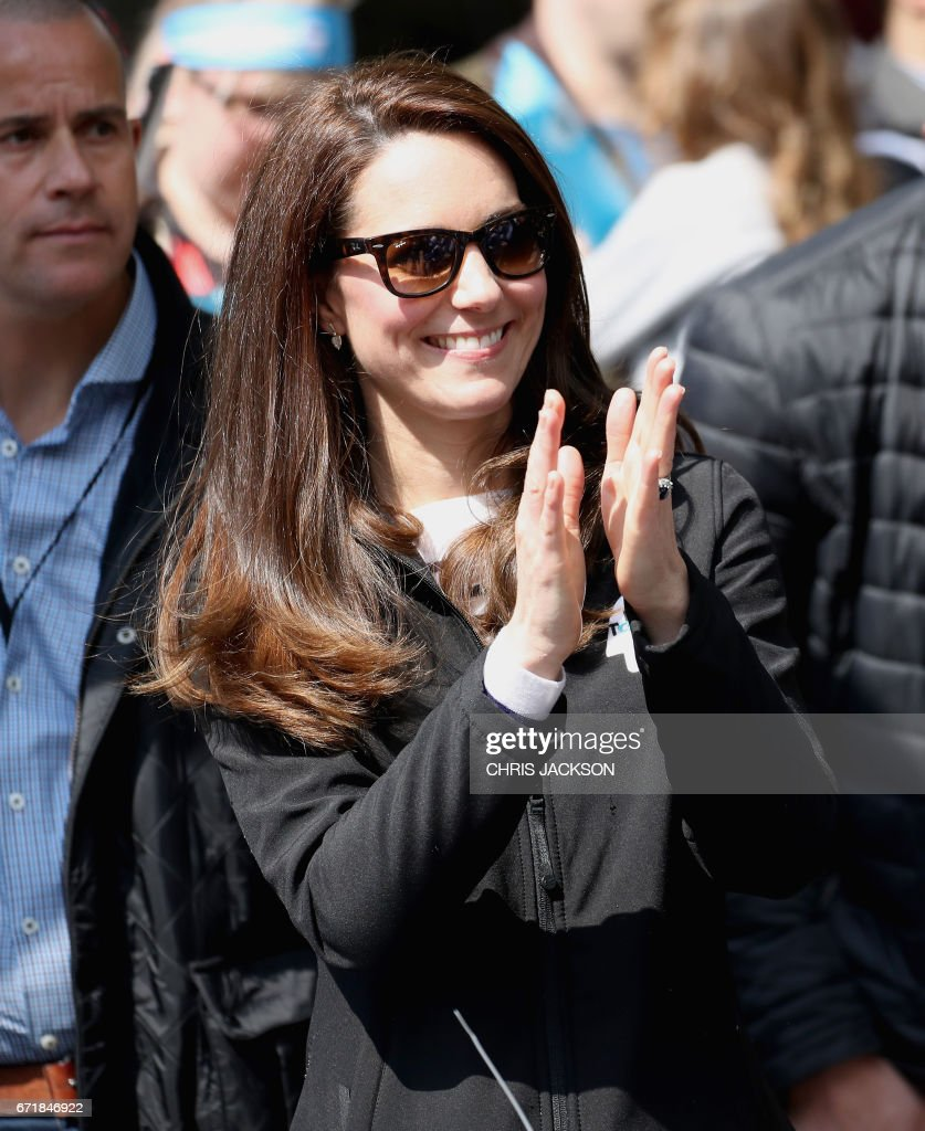 Britain's Catherine, Duchess of Cambridge cheers and hands out water to runners during the 2017 London Marathon in London on April 23, 2017. / AFP PHOTO / POOL / Chris Jackson