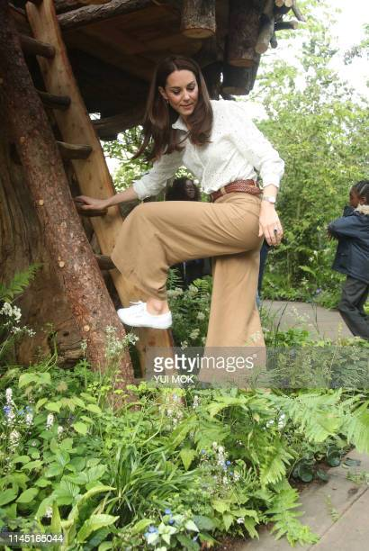 Britain's Catherine Duchess of Cambridge climbs a ladder into a treehouse as she visits the 'Back to Nature Garden' garden that she designed along...