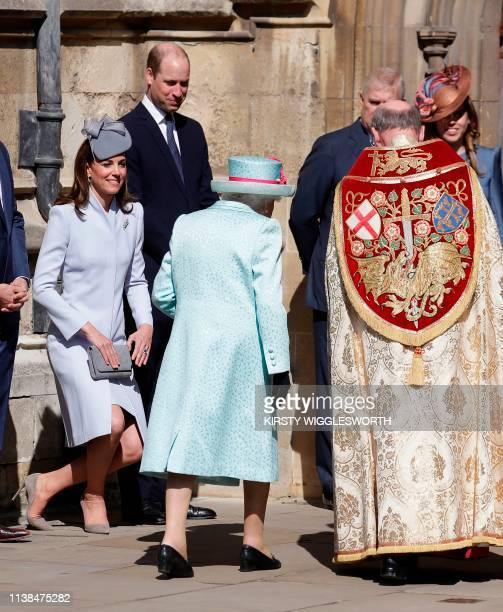 Britain's Catherine Duchess of Cambridge curtsies as Britain's Queen Elizabeth II arrrives for the Easter Mattins Service at St George's Chapel...