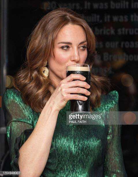 Britain's Catherine Duchess of Cambridge drinks a pint of Guinness during as she attends a special reception at the Guinness Storehouses Gravity Bar...