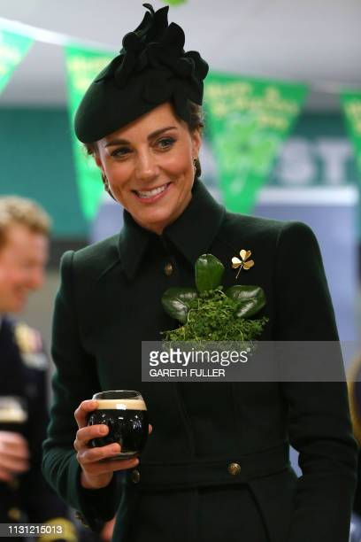 Britain's Catherine Duchess of Cambridge enjoys a pint of Guinness with officers and guardsmen of the 1st Battalion Irish Guards after the St...