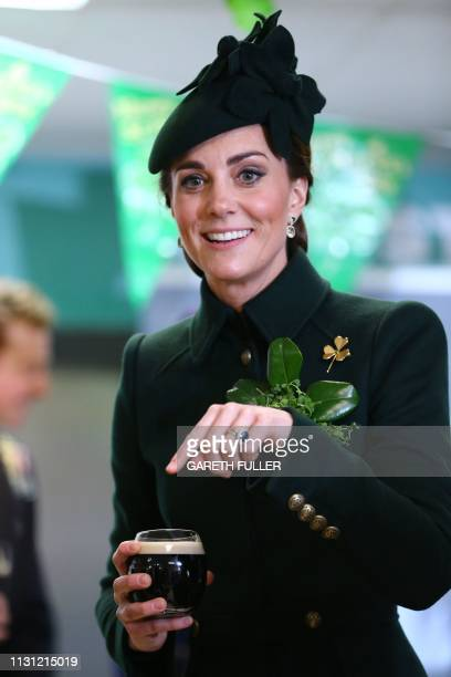 Britain's Catherine, Duchess of Cambridge enjoys a pint of Guinness with officers and guardsmen of the 1st Battalion Irish Guards after the St...