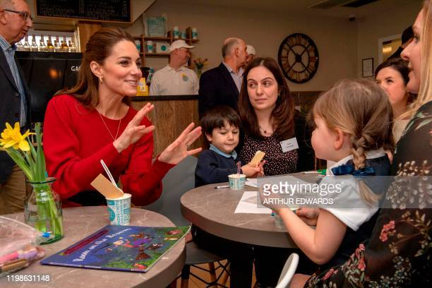 Britain's Catherine Duchess of Cambridge gestures as she meets with local parents and carers during her visit with her husband Britain's Prince...