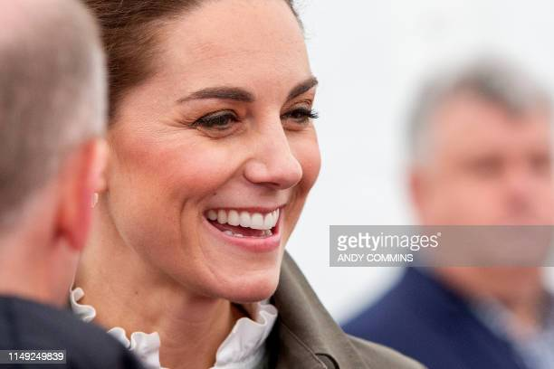 Britain's Catherine Duchess of Cambridge gestures during a visit to the market town of Keswick north west England on June 11 where they joined a...