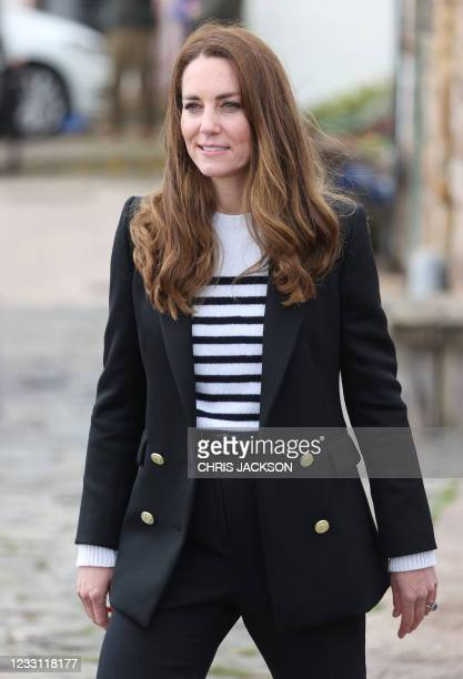 Britain's Catherine, Duchess of Cambridge gestures during a visit to meet local fishermen and their families and hear about the work of fishing...