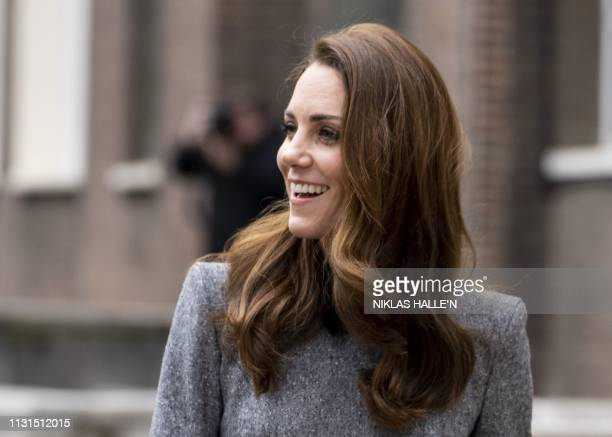 Britain's Catherine Duchess of Cambridge gestures to onlookers on her arrival to visit the Foundling Museum where young people are taught to use art...