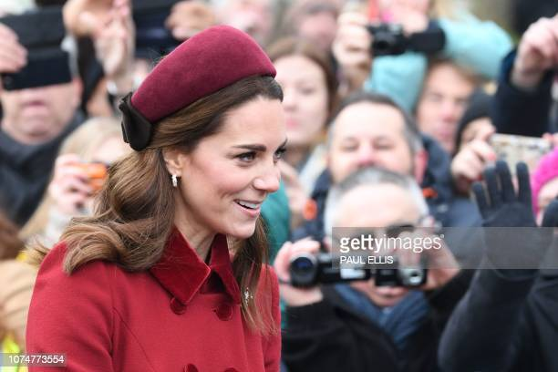 Britain's Catherine Duchess of Cambridge greets the crowds as she leaves the Royal Family's traditional Christmas Day service at St Mary Magdalene...