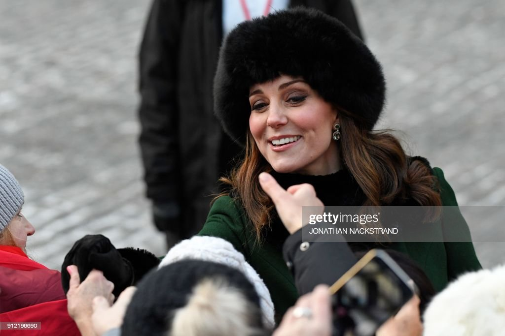 Britain's Catherine, Duchess of Cambridge greets wellwishers as she and Prince William, Duke of Cambridge (not in picture) walk through the cobbled streets of Stockholm from the Royal Palace to the Nobel Museum on January 30, 2018. The Duke and Duchess of Cambridge are on a 4-day visit to Sweden and Norway. / AFP PHOTO / Jonathan NACKSTRAND