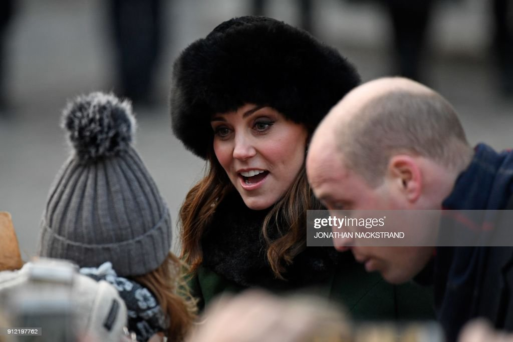 Britain's Catherine, Duchess of Cambridge (C) greets wellwishers as she and Prince William, Duke of Cambridge (R) walk through the cobbled streets of Stockholm from the Royal Palace to the Nobel Museum on January 30, 2018. The Duke and Duchess of Cambridge are on a 4-day visit to Sweden and Norway. / AFP PHOTO / Jonathan NACKSTRAND
