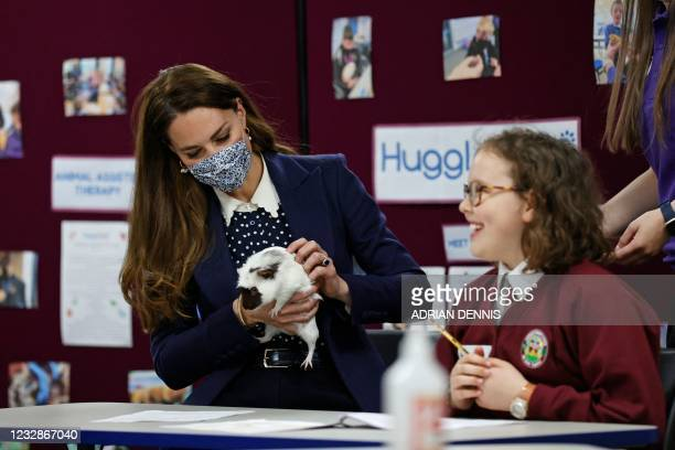 Britain's Catherine, Duchess of Cambridge, handles Gus the Guinea Pig as she joins a group of local school children from Loxdale Primary School...