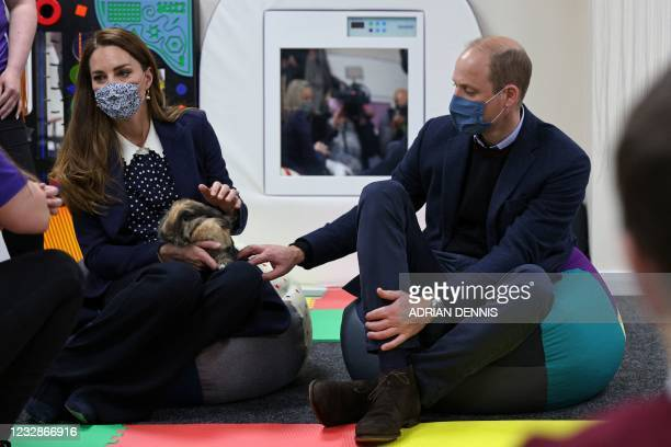 Britain's Catherine, Duchess of Cambridge handles Milly the rabbit as she and Britain's Prince William, Duke of Cambridge join a group of local...