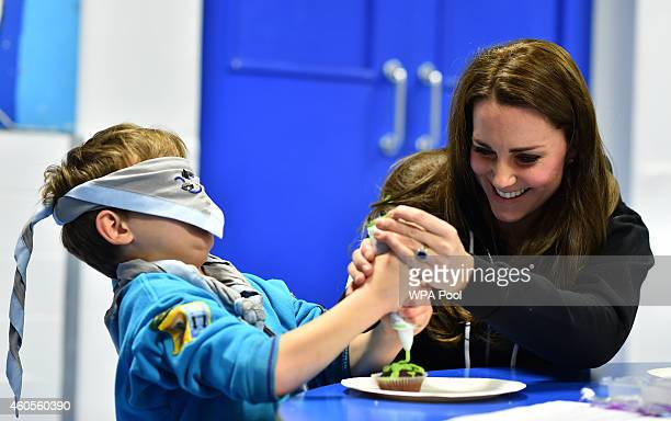 Britain's Catherine Duchess of Cambridge helps a blindfolded boy ice a cake as she promotes disability awareness while meeting with children at the...