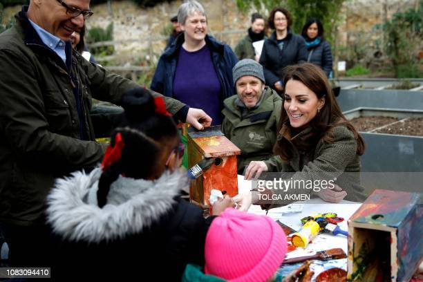 Britain's Catherine Duchess of Cambridge helps build a bird box with children as she visits the Islington community garden in north London on January...