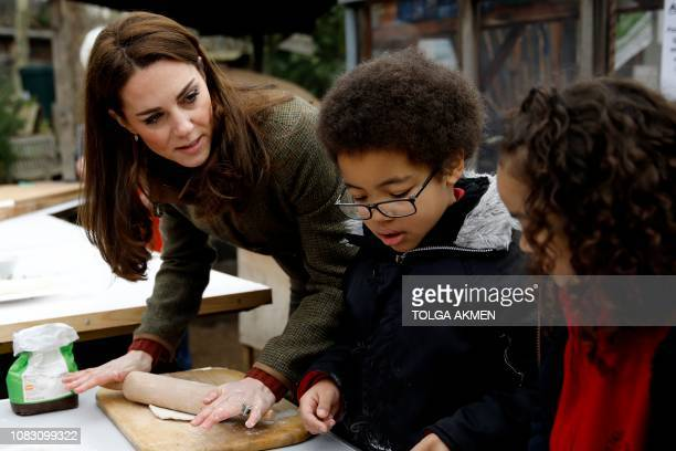 Britain's Catherine Duchess of Cambridge helps make pizza as she visits the Islington community garden in north London on January 15 2019