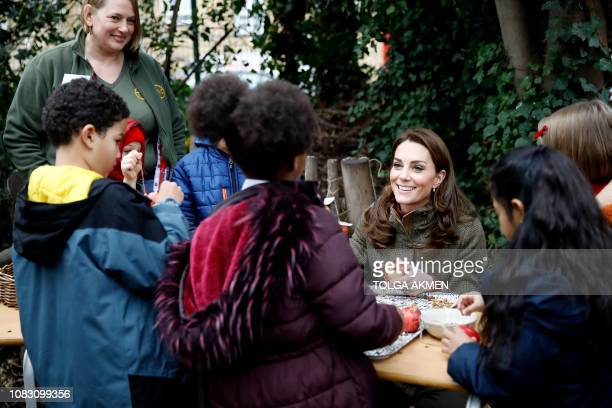 Britain's Catherine, Duchess of Cambridge helps make winter bird feed as she visits the Islington community garden in north London on January 15,...