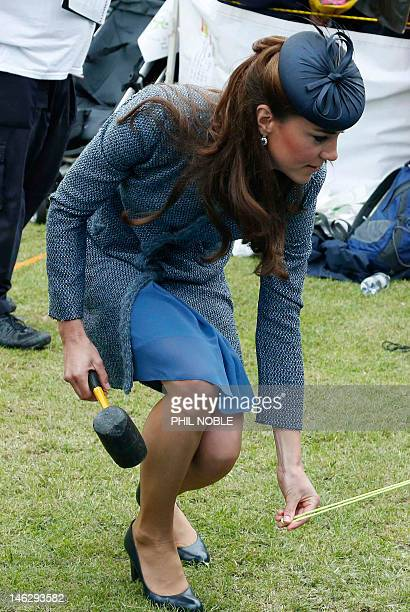 Britain's Catherine Duchess of Cambridge helps scouts to pitch a tent during a visit to Vernon Park in Nottingham central England on June 13 2012 The...